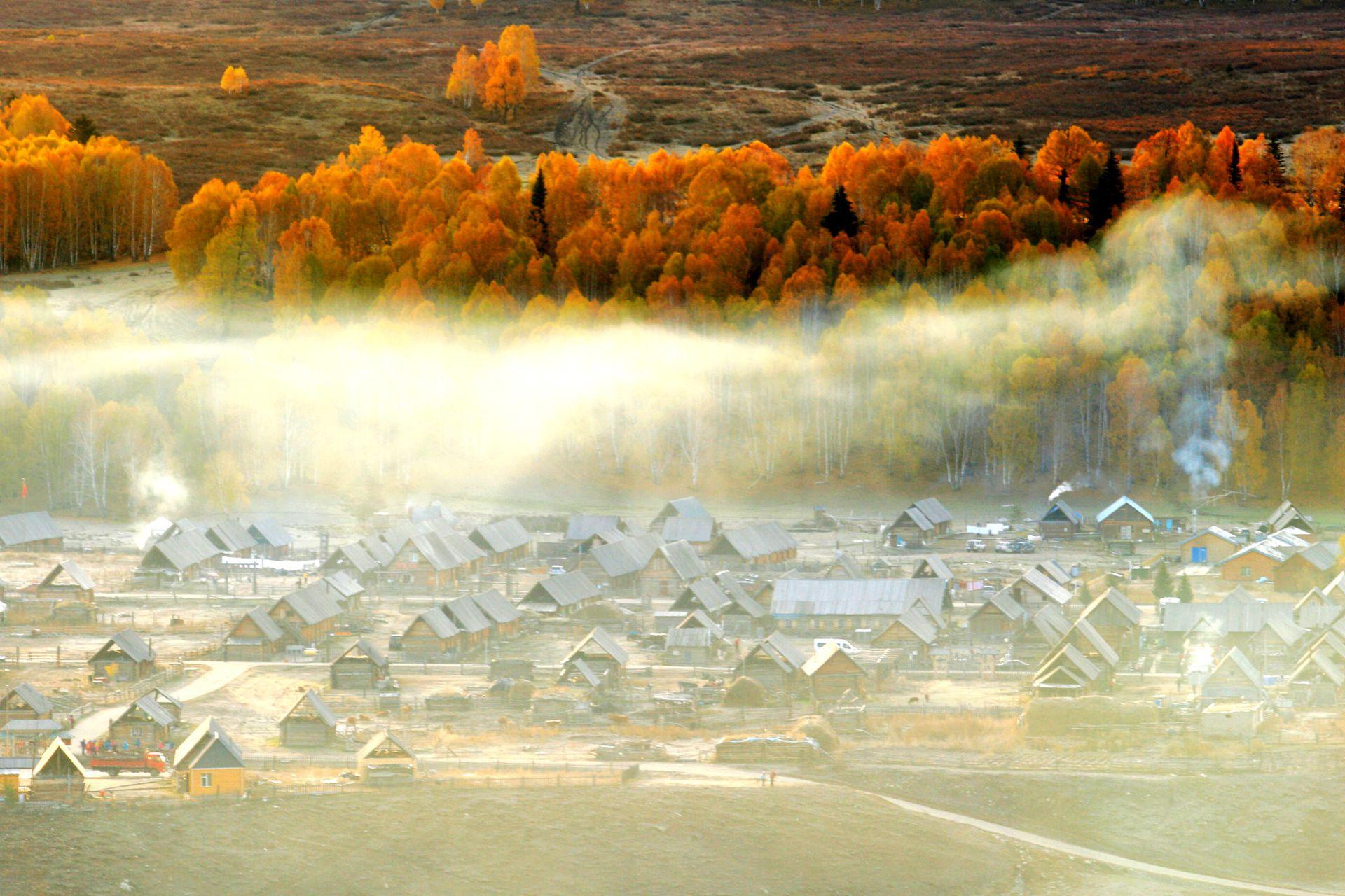 """禾木村是中国新疆布尔津县下辖的一座村庄。位于新疆布尔津县喀纳斯湖畔,是图瓦人的集中生活居住地。它素有""""中国第一村""""的美称。原木搭建的小木屋散落在新疆喀纳斯湖旁的土地上。禾木村最出名的就是万山红遍的醉人秋色,炊烟在秋色中冉冉升起,形成一条梦幻般的烟雾带,胜似仙境。(视觉中国)"""