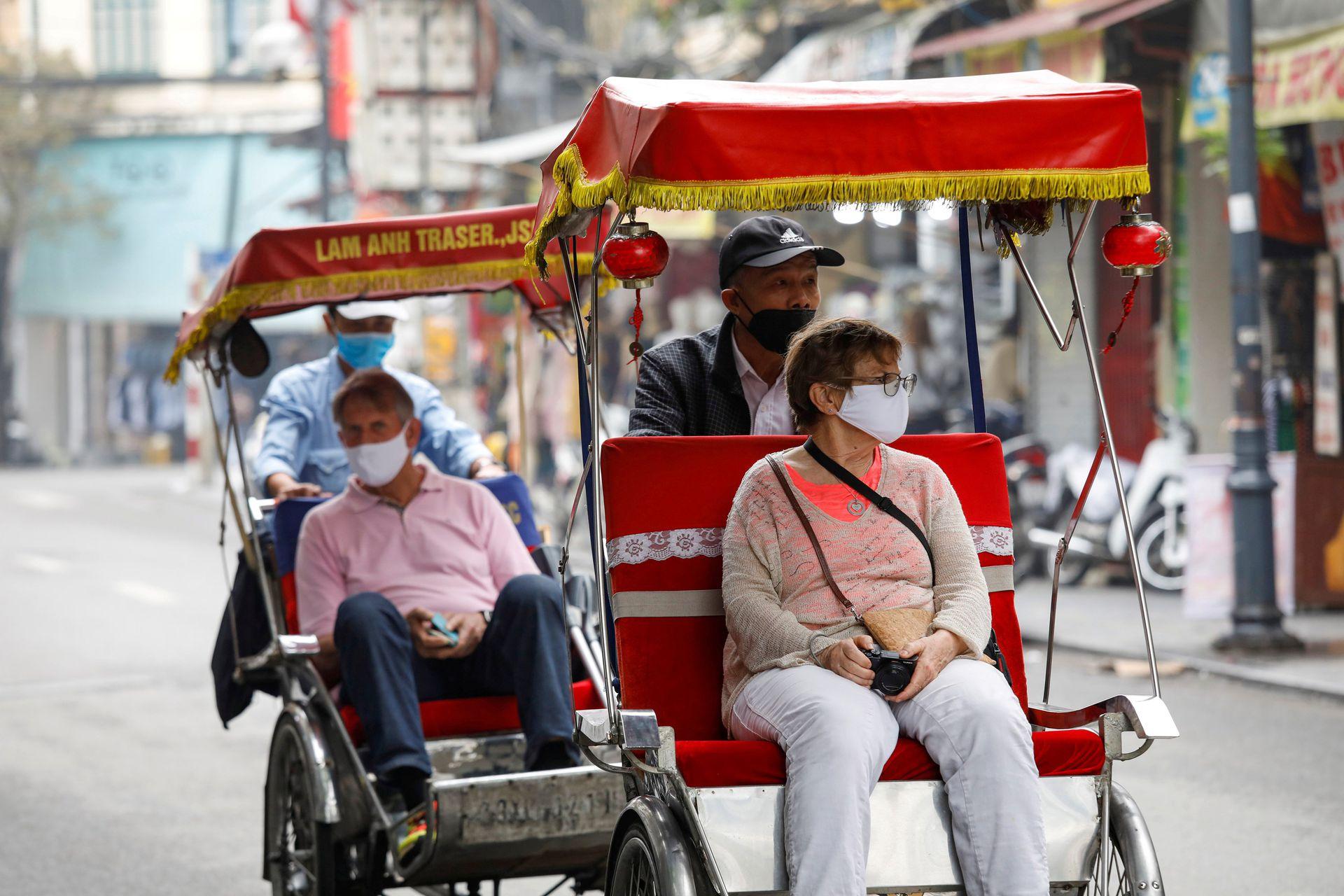 两名外国游客在2020年3月时戴着口罩,搭乘载客三轮车徜徉于越南河内老城区的街道。此后,越南开始了更为严格的封闭与防疫措施,到2020年6月,越南全境只接纳了约九千名外国旅游者。此举虽然让越南的旅游业陷入冰点,但对国内防疫态势形成了有效的帮助。(路透社)
