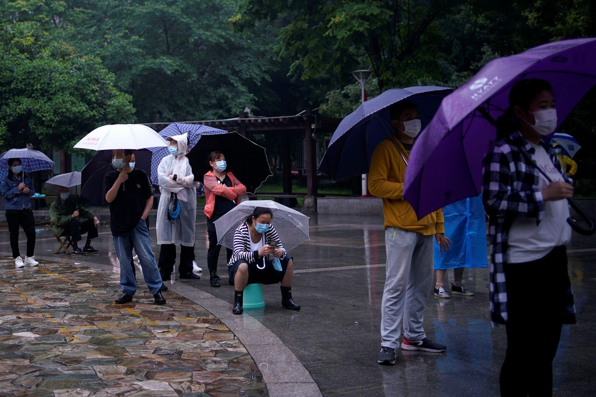 5月14日武汉,居民们戴着口罩在雨中排队进行核酸检测。(Reuters)