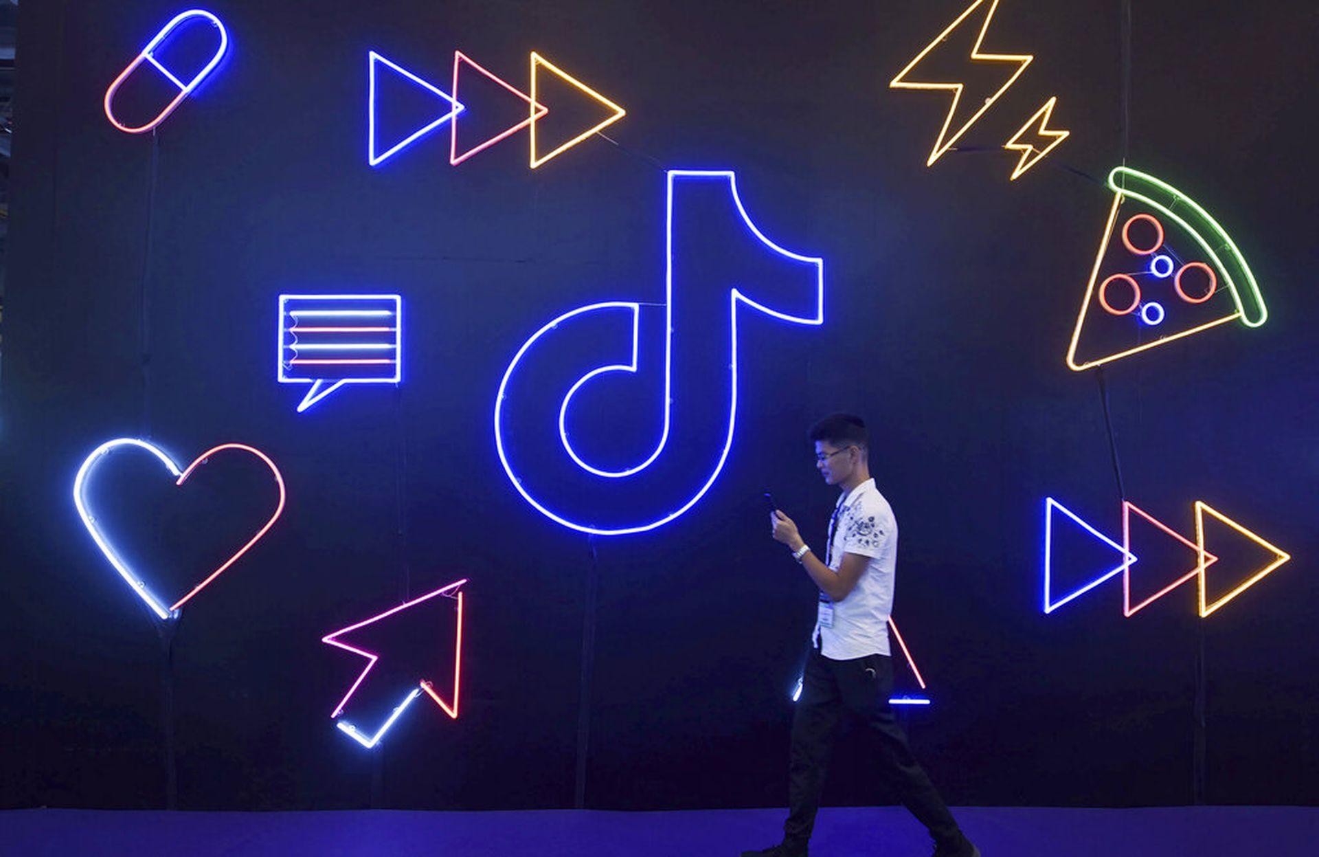 TikTok是抖音国际版,在中国与国外拥有众多粉丝。图为2019年10月18日,一名男子参加在中国杭州市举行的博览会,场内有一个抖音的灯光装置。(AP)